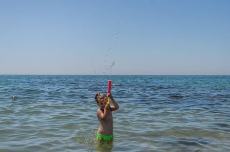 Little charming girl child plays in the sea and sprays a water gun Banque d'images