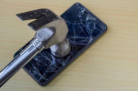 A hammer breaks the screen of a smartphone