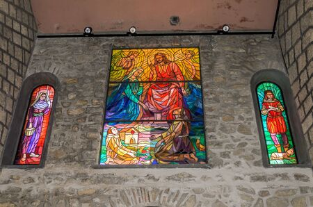 ROMA, ITALY - JULY 2019: Religious multi-colored mosaics on the windows of the church in Greccio where St. Francis of Assisi held the first nativity scene