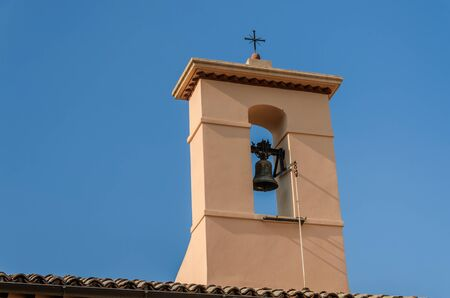Old antique bell tower with a cross on a background of blue sky Imagens