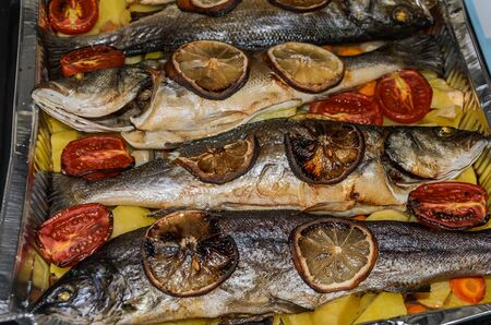Roasted fish with vegetables and lemon in aluminum form