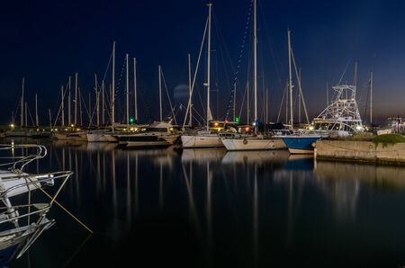 Night port with luxury sailing yachts
