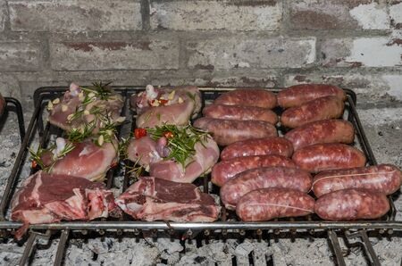 Raw meat grilled on the grill in the fireplace