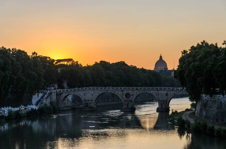 Sunset on the background of the bridge over the Tiber in Rome overlooking the dome of St. Peters basilica in the vatican Imagens