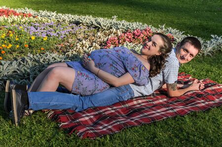 Young happy family, husband and pregnant wife lie on the grass on a bedspread in a park Stock Photo