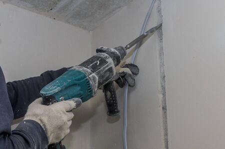 Worker breaks a concrete wall with a perforator chisel