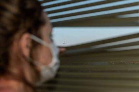 Woman in medical mask looks out the window through the blinds at the church cross