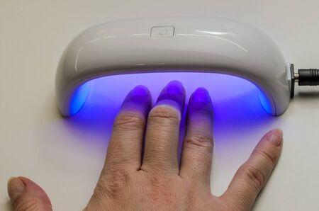 Woman dries gel nail polish under ultraviolet lamp Stok Fotoğraf
