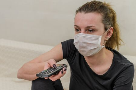 A young girl in a medical mask switches channels on the TV with a remote control Stock Photo