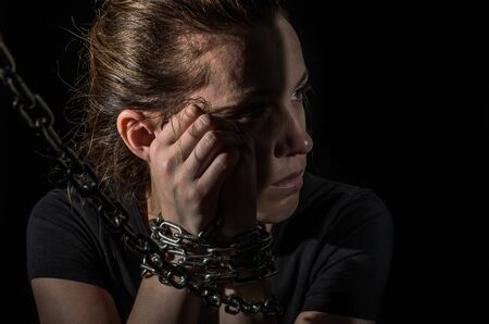 Young woman blindfolded in chains breaks out of them on a black background