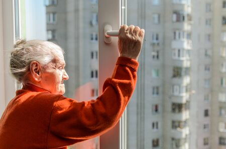 An elderly woman opens a window on a sunny day