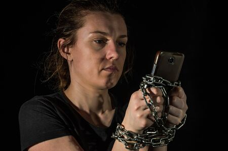 Young woman with chain tied hands to smartphone on black background