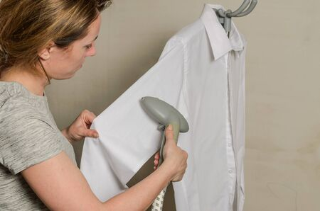 Woman ironing shirt with steam iron