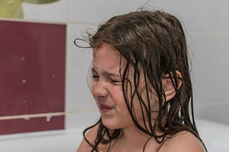 Little charming baby girl bathes in a bath with foam