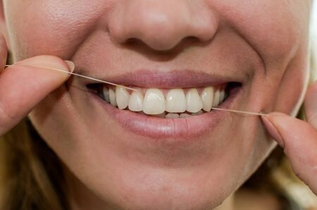 Young girl flossing her teeth