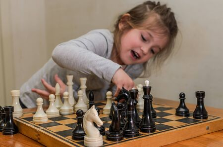 Little charming girl child playing chess