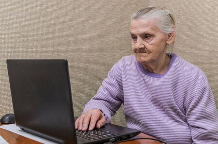 An elderly woman communicates on a laptop via video calling