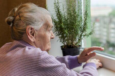 Elderly woman looking out the window Foto de archivo