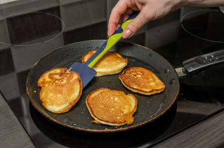 Pancakes are fried in a pan on an induction stove