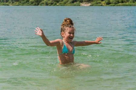 Little charming girl child bathes in a lake and plays splashing water