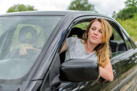 Young charming girl driving a black car