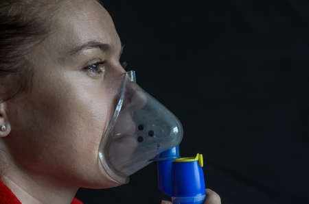 Woman breathing into mask while making inhalation on black background 版權商用圖片