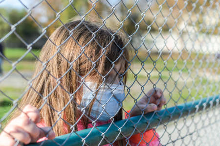 Little girl child in medical mask behind an iron fence