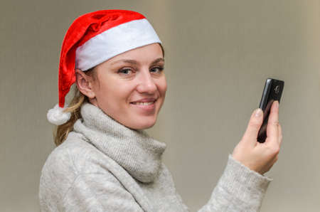 Young girl in santa claus hat talking on video communication with her friend