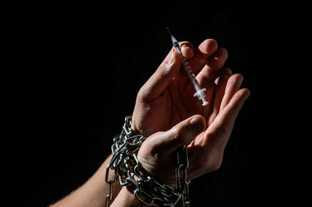 Human hands chained with a syringe for injection isolated on black background