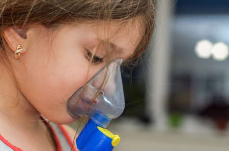 Little girl child makes inhalation with mask on face Archivio Fotografico