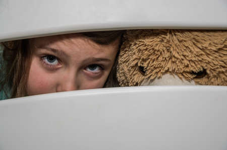 Little adorable girl child with a teddy bear looks through a crack in a hole in a wooden fence Archivio Fotografico
