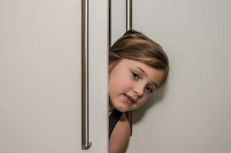 Little adorable girl child peeking out of the cabinet doors