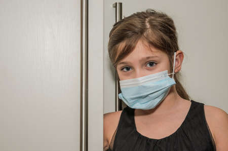Little girl child in medical mask peeks out of the door