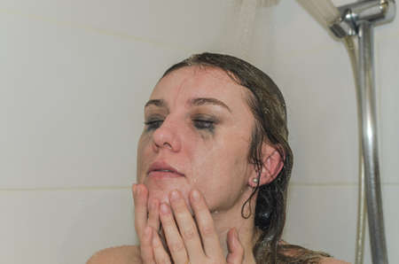 Young charming woman washes off mascara from her eyes in the shower