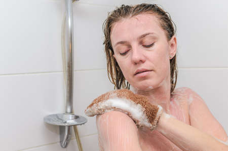Young charming woman makes a scrub in the bathroom with a special washcloth on her hand