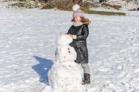 Little adorable girl child sculpts snowman from snow in winter Archivio Fotografico
