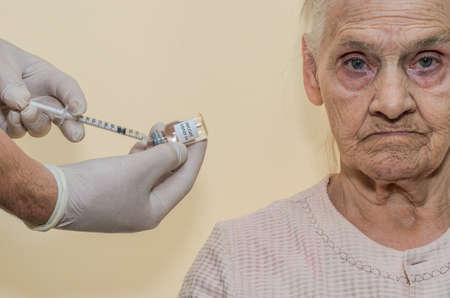An elderly woman is being vaccinated against the virus Archivio Fotografico