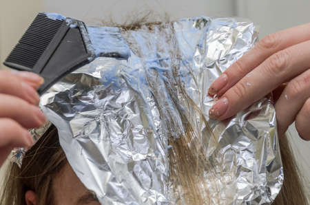 Young woman dyes her hair
