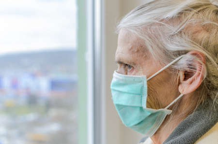 Elderly woman in medical mask looking out the window
