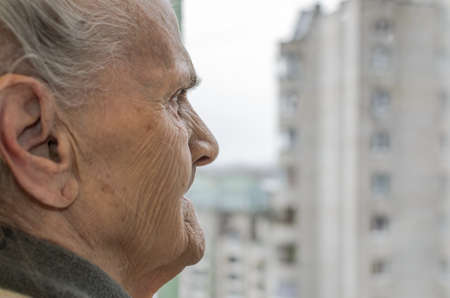 An elderly woman looking out the window