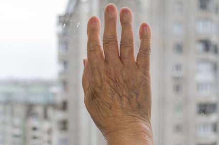 Elderly woman's hand on the window