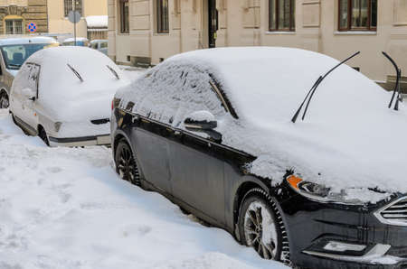 In winter, on a snow-covered street there are cars covered with snow