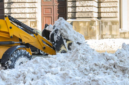 Snow removal tractor clears the road from snow Archivio Fotografico