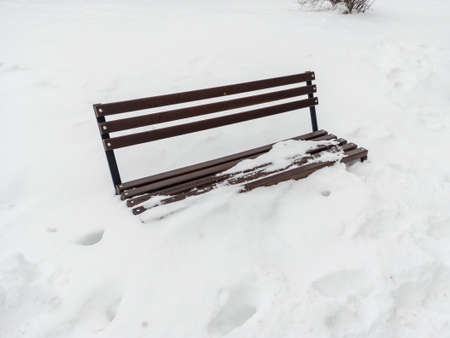 Park bench covered by snow