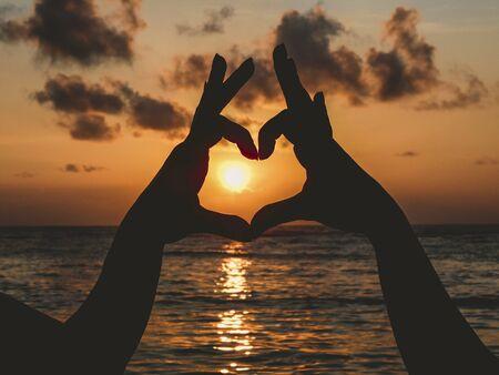 les mains font coeur au coucher du soleil