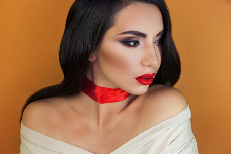 a beautiful girl with sensual bright red lips on an orange background, a red ribbon on her throat does not leave anyone indifferent, everyone looking into her brown eyes