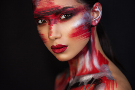 the Euro-Asian woman looks directly at us, on a black background, sensual red lips are closed, red silver black makeup emphasizes her image Фото со стока
