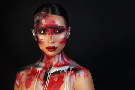 the Euro-Asian woman looks away on a black background with bright red lips, unusual make-up with red, silver threads Standard-Bild