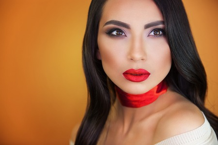 beautiful portrait of a girl with red lips and red ribbon around her neck made by professional makeup Фото со стока