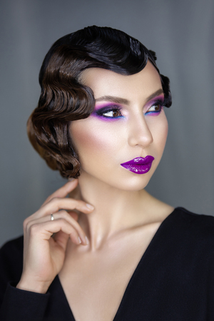 feminine image and films of the 1920s, glamorous girl with purple lips, and Finger wave hairstyle Фото со стока